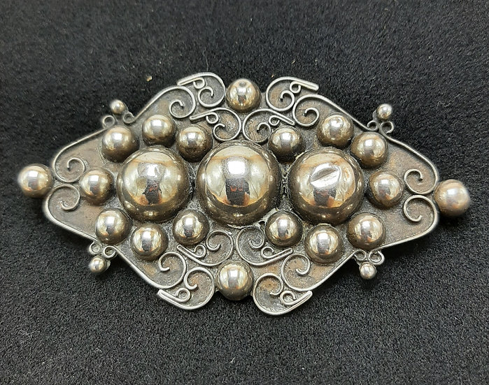 Sterling pin with raised relief domes