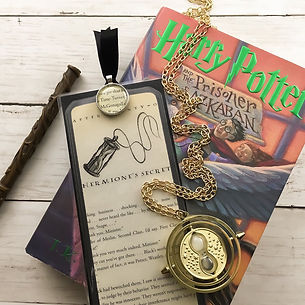 Handmade bookmark made from Harry Potter chapter pages shown with Harry Potter and the Prisoner of Azkaban book and movie props including Hermione's wand and time turner necklace