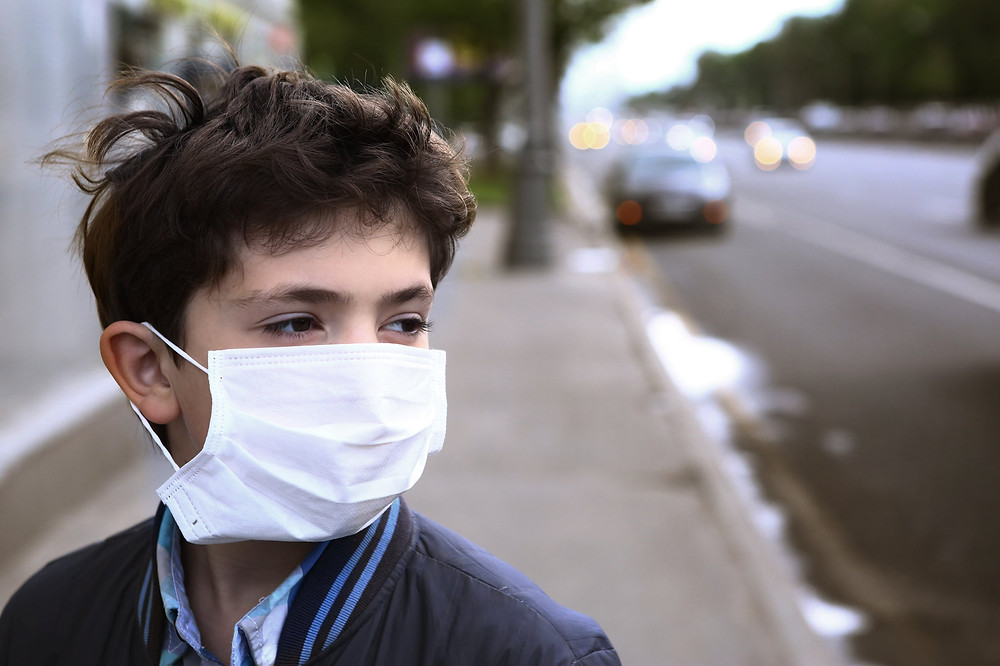 Young boy with face mask on. From Getty Images