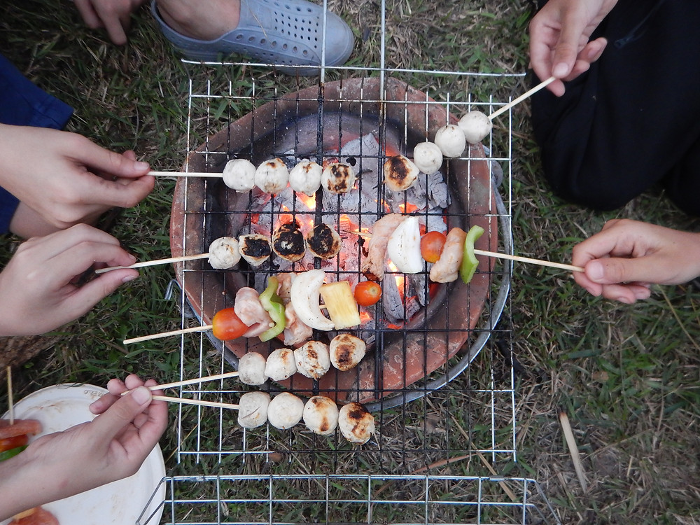 Cooking on an open BBQ with children during an outdoor education camp.