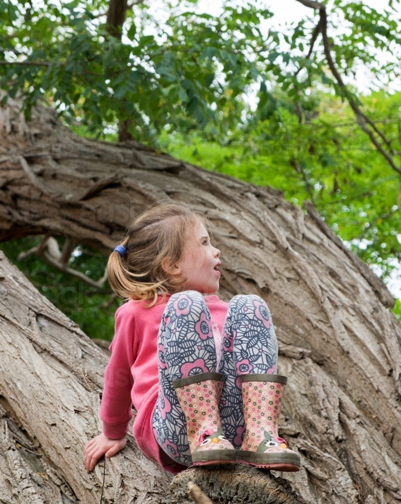 A young girl climbs a tree while happily playing outdoors