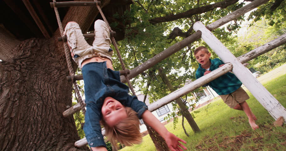 Child hanging upside down outdoors.