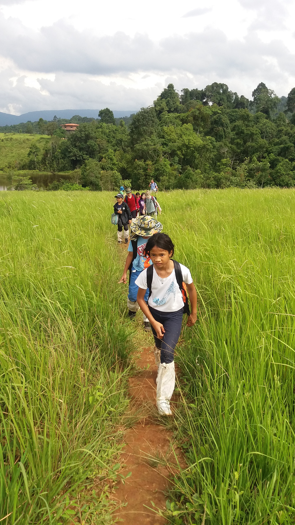 Children hiking outdoors in  grassland environment in Thailand.