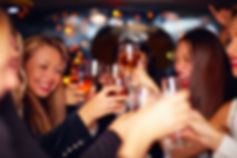 beautiful women clinking glasses in limo