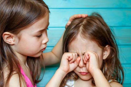 Girl rubbing her teary eyes