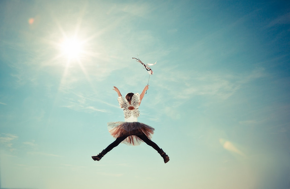 Meisje met engelenvleugels en een staf zweeft in de lucht.