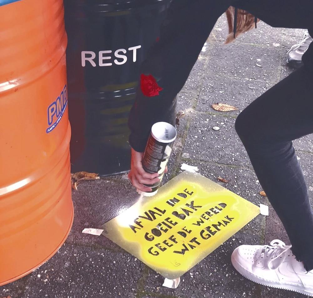 Leerling van Vitusmavo spuit graffiti op de stoep met de tekst: afval in de goede bak geeft de wereld wat gemak.