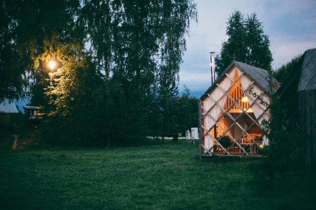 Een klein houten huis met twee woonlagen in de natuur.