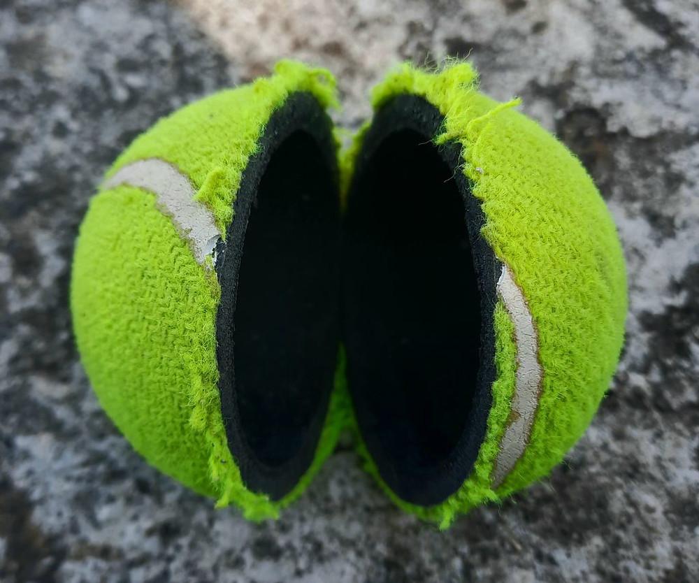 A broken tennis ball exposing hollow core