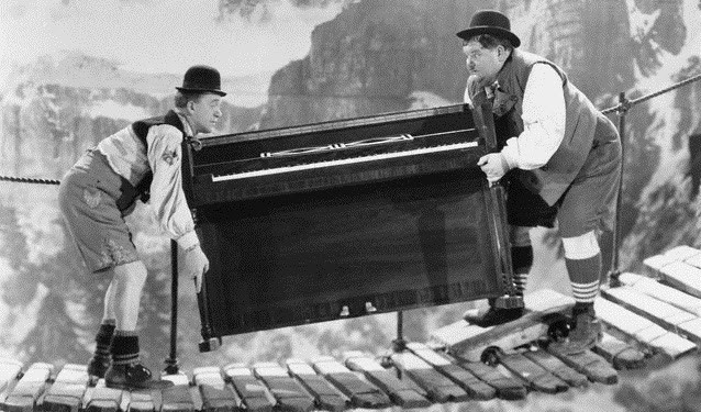 two people moving a piano