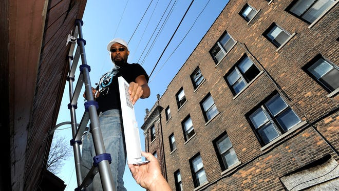 Ali Dirul of Detroit, Ryter Cooperative Industries Engineering Director, prepares to install the solar-powered LED light on the garage to light up the alleyway. Todd McInturf The Detroit News.