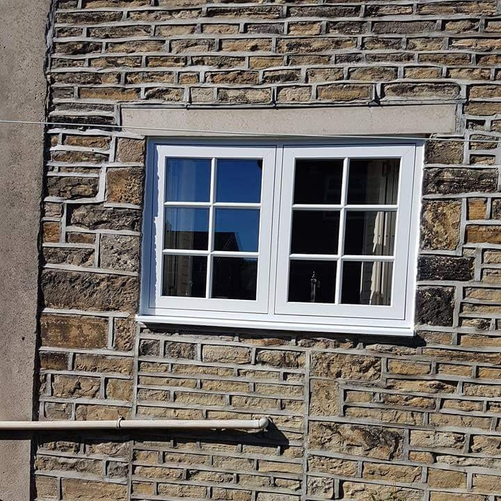 A white UPVC double glazed flush casement window finished in white wood grain