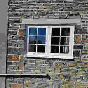 A white UPVC double glazed flush casement window finished in white wood grain