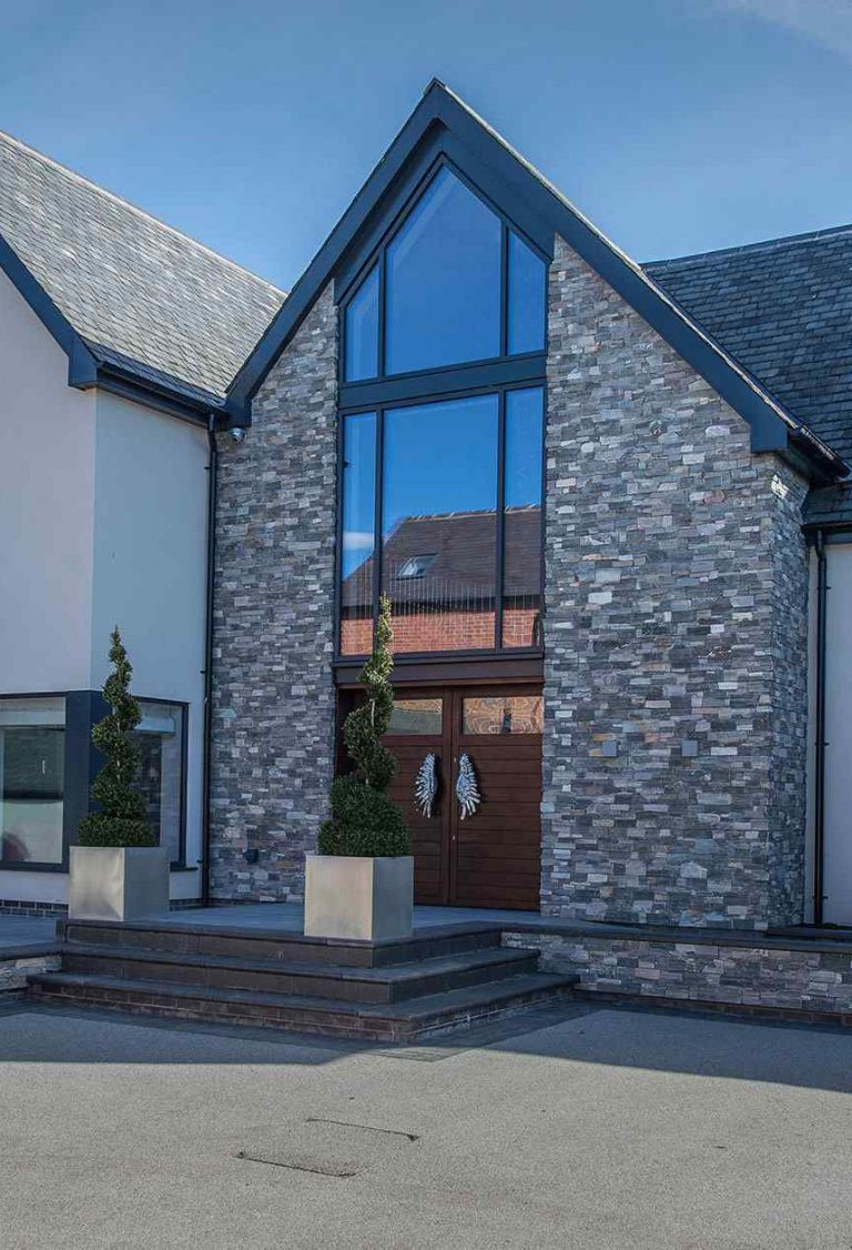 A large aluminium window and curtain wall featuring large glass panes painted in anthracite grey