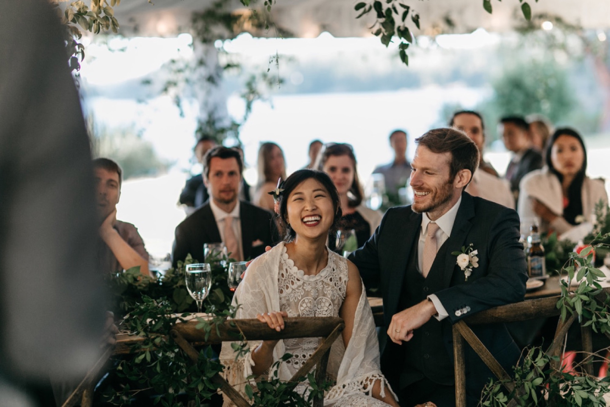 Bride and groom laughing during toasts at a Pebble Cove Farm Wedding