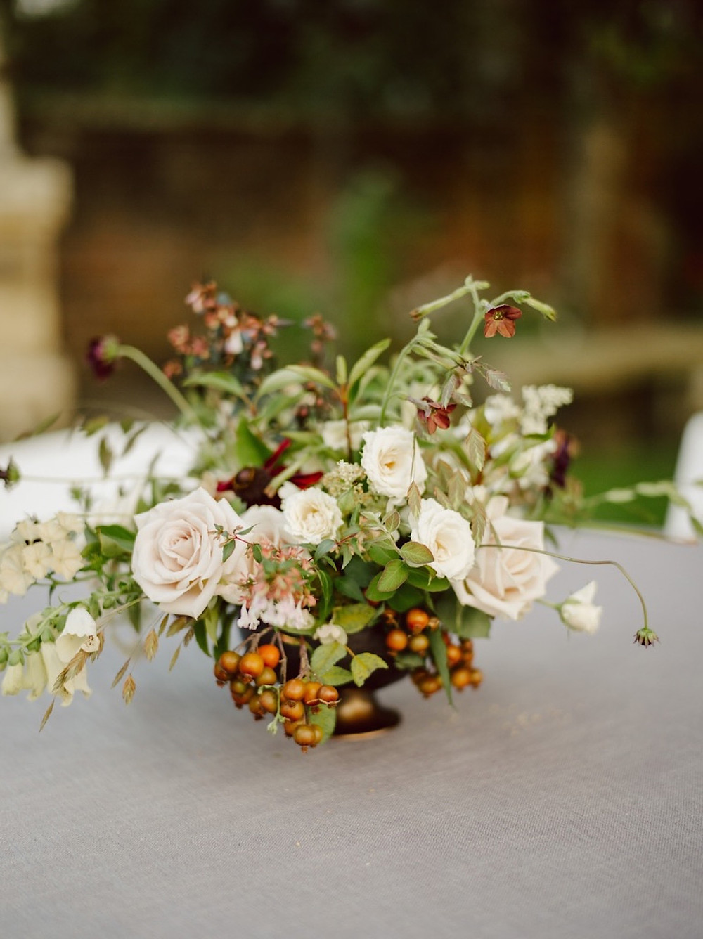 Wedding reception centerpiece at Thornewood Castle with cream, dusty rose, and burgundy tones