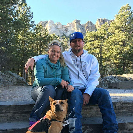 couple nd heeler in font of mount rushmore