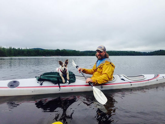 puppy and man on kyack in water