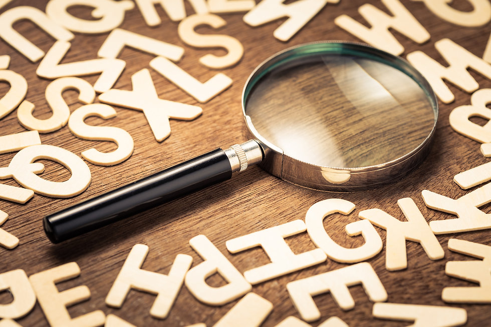 Magnifying glass with many wood letters