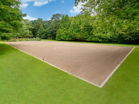 Regulation sized outdoor dressage arena nestled under aged and carefully manicured vegetation.