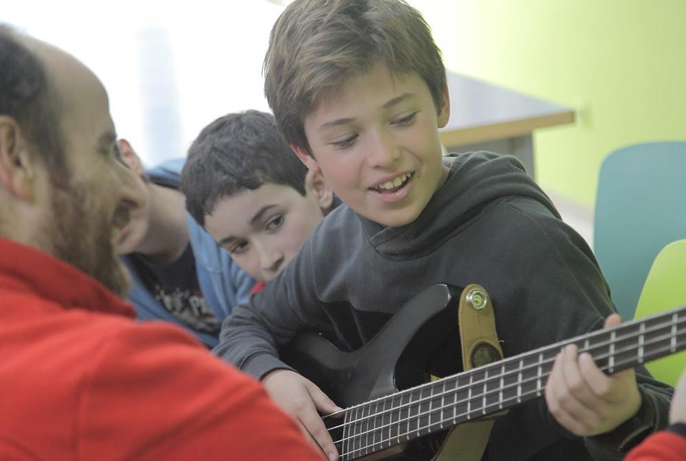 Profesor enseñando a tocar el bajo