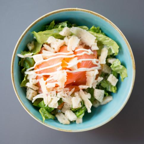 Ceasar salad salmone canadese  con iceberg, crostini di pane croccante, ceasar dressing e scaglie di Parmigiano Reggiano