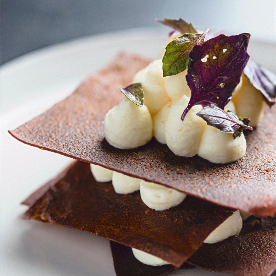 Millefoglie fermentato: Sfoglia di patate americane e fave di cacao, crema pasticcera di ricotta al limone fermentato, basilico rosso