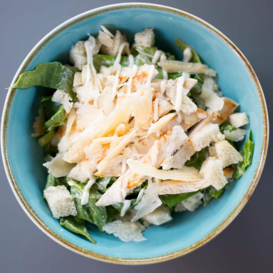 Ceasar salad pollo con iceberg, crostini di pane croccante, ceasar dressing e scaglie di Parmigiano Reggiano