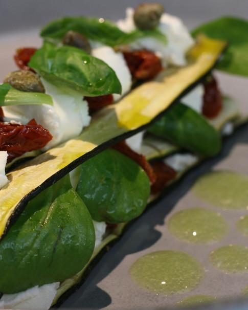 Parmigiana estiva di zucchine in soia, caprino, pomodori secchi, capperi e mais tostato