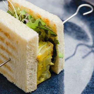 Mr Potatoes Tamago Sando: Sandwich di pane bianco ripieno di frittata di patate fermentate, cetrioli, insalata aromatica e salsa chimichurry