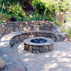A hillside patio with a small pond, fire pit and generous seating.