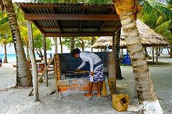 young man doing BBQ on Moho Caye