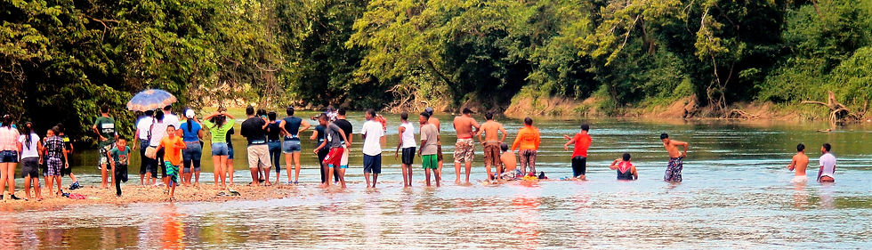 people stand and swimming at the Belize River