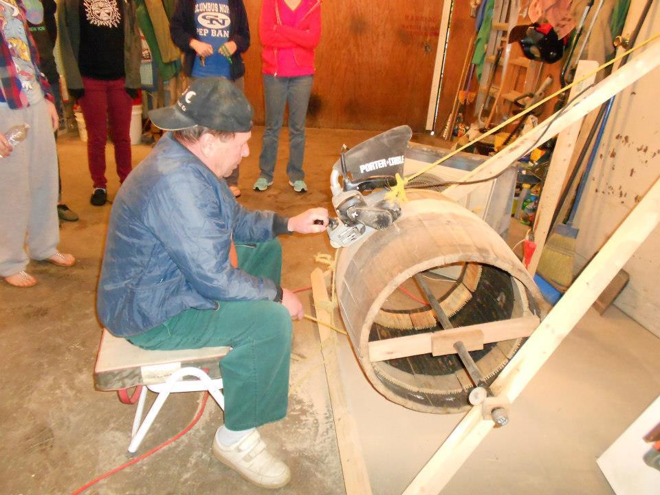 Master Builder Peter Sulivan sands a barrel