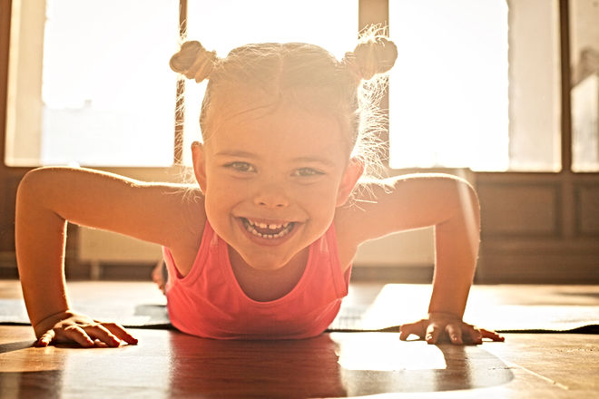 Little girl workout at home. Looking at