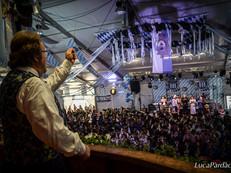Il Maestro Fiorenzo Brigadoi dirige le Bande all'Oktoberfest di Predazzo. © Foto di Luca Pardac.