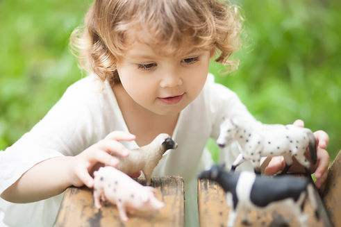 Cute toddler girl playing with farm anim