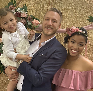 A man, woman, and young girl; all smiling while dressed for a wedding.