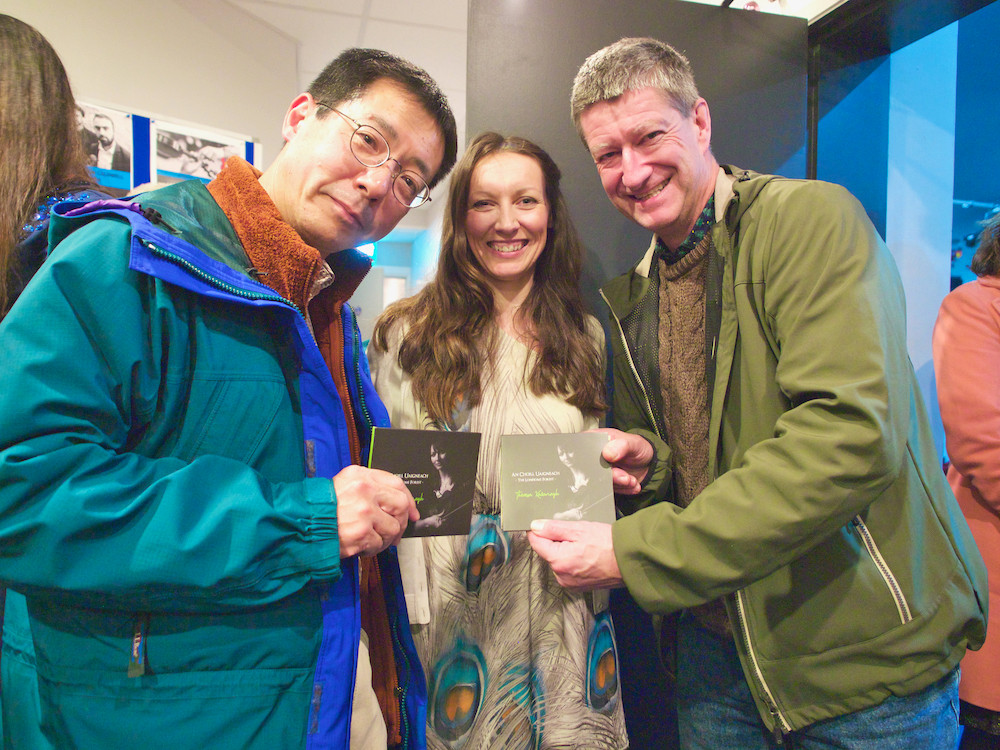 Toru Kumagai (l) from Japan and Reuben Ó Conluain (r) congratulate fiddle player, Theresa Kavanagh, on release of her new CD 'An Choill Uaigneach' (The Lonesome Forest).