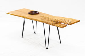 """Reclaimed white ashslab style coffee tablewith ahand-turned mahogany bowel recessedinto the top, as well asa hand-carved river pattern. Withblack hairpin legs. 49"""" wide, 17"""" deep, 17"""" tall, 1"""" thick. Mahogany bowel measures 7"""" in diameter."""