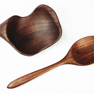 """This Isamu Kenmochi Inspired spoon and spoon rest was hand-carved and shaped out of reclaimed black walnut. Finished with a matte/satin furniture oil that is both vegan friendly and 100% food-safe, this finish can easily be recoated if needed. The spoon measures  11"""" long by 3"""" wide.  Bowl measures  8"""" long by 5.5"""" wide and is 1.75"""" tall."""
