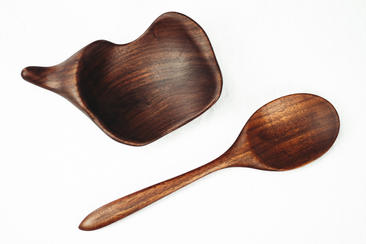 """ThisIsamu KenmochiInspired spoon and spoon rest was hand-carved and shaped out of reclaimed black walnut.Finished with a matte/satin furniture oil that is both vegan friendly and 100% food-safe, this finish can easily be recoated if needed. The spoon measures11"""" long by 3"""" wide. Bowl measures8"""" long by 5.5"""" wide and is 1.75"""" tall."""