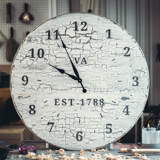 """We're starting to design and handcraft a handful of home goods products inspired by early American painted furniture. This 32"""" inch oversized wall clock features a faux white over black paint crackle paint job. The cracks are not done by stencil or by being brushed on, and we used a safe and stable method to make the paint crackle as we apply it. We can achieve the """"rustic cracked paint look"""" in a way so that our clients won't have to deal with all the flaking, chipping, and possible health hazards of old cracked paints. This is a product that has a lot of custom-order potential, if you are looking for something specific, feel free to send us a message.  The simple clock works are powered with one AA battery."""