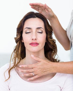 Calm woman receiving reiki treatment on