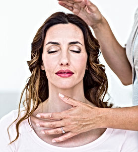 Calm woman receiving reiki treatment on