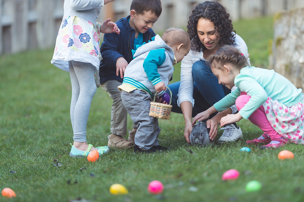 Kids and an adult having an Easter egg hunt