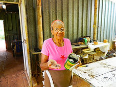 An elder woman in a pink shirt and glasses offers a handful of seeds pulled from an old coffee can.