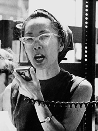 Black and white photo of Yuri Kochiyama speaking into a loudspeaker microphone.