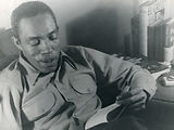 A black and white photo of Ernest Thompson smiling, leaning back in a chair reading.