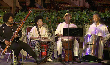 Joey Guidre plays bassoon next to three seated drummers, Chioneso Bakr, Victor See Yuen, and Hasan Bakr who sings.